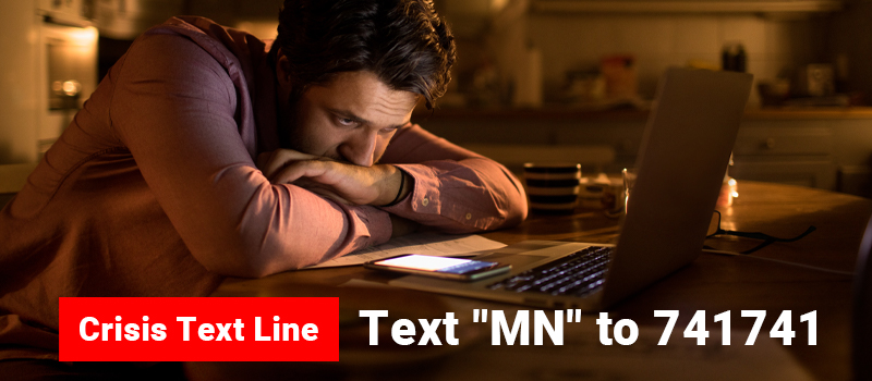 Male looking at cell phone with text of Crisis Text Line - Text MN to 741741