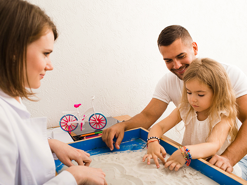 Child and father playing in sand with counselor