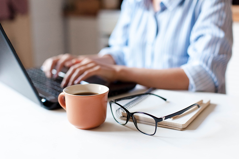 Close up of lady typing on laptop with coffee cup, glasses and notebook