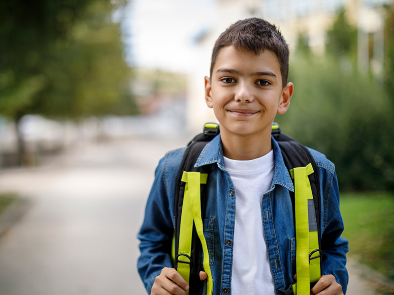 Young Boy holding backback while walking and smiling